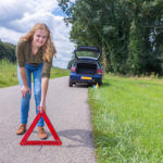 Woman placing warning triangle on road