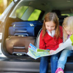 Children using a map in the back of a car