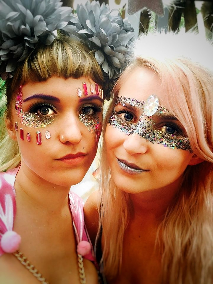 Two women at a festival with face jewels and glitter