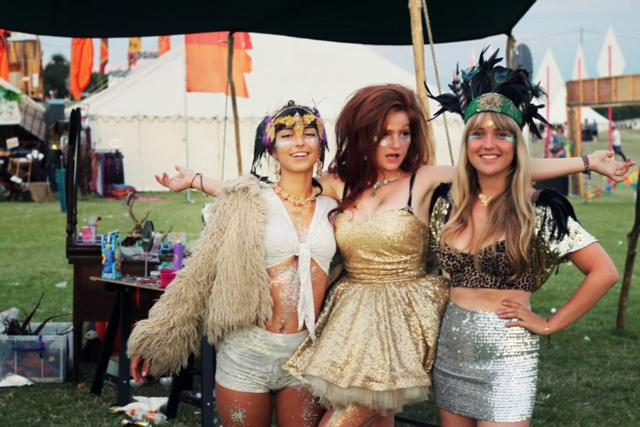 Three women at a festival with gold glitter and sequined outfits