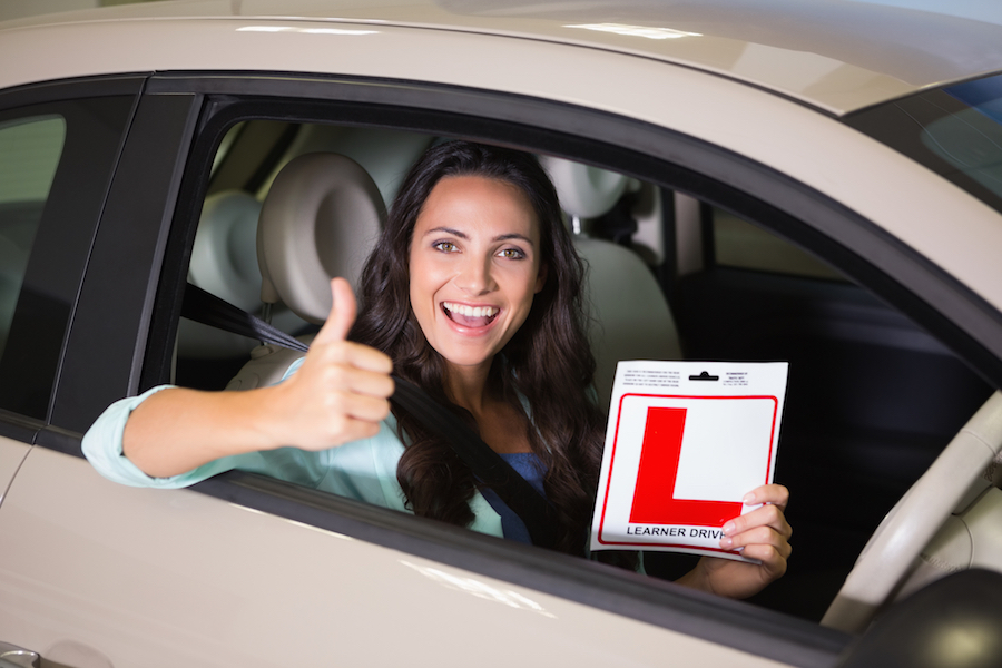 woman holding learner driver sign